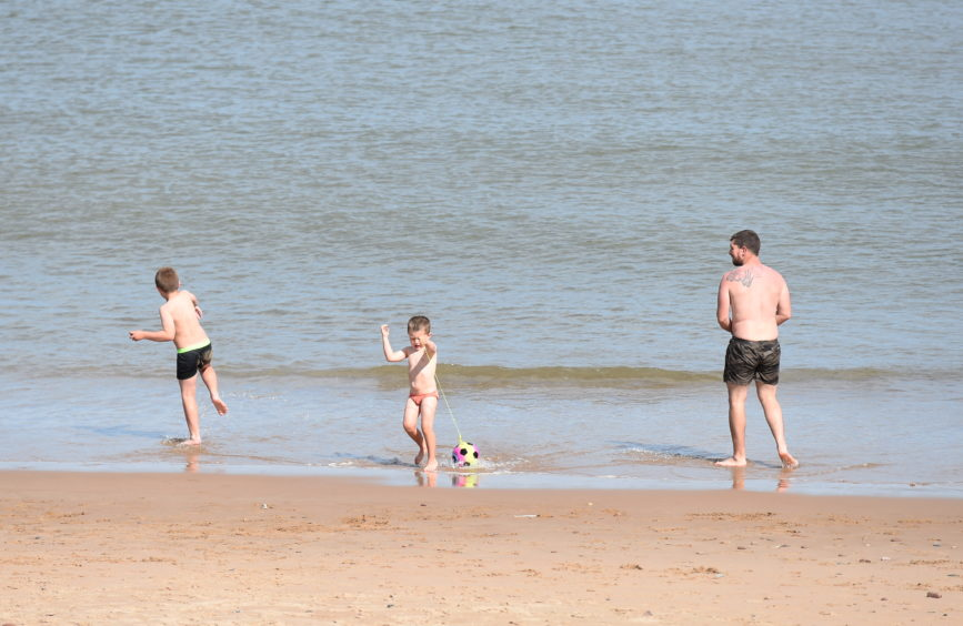 A family playing in the surf on Aberdeen Beach
