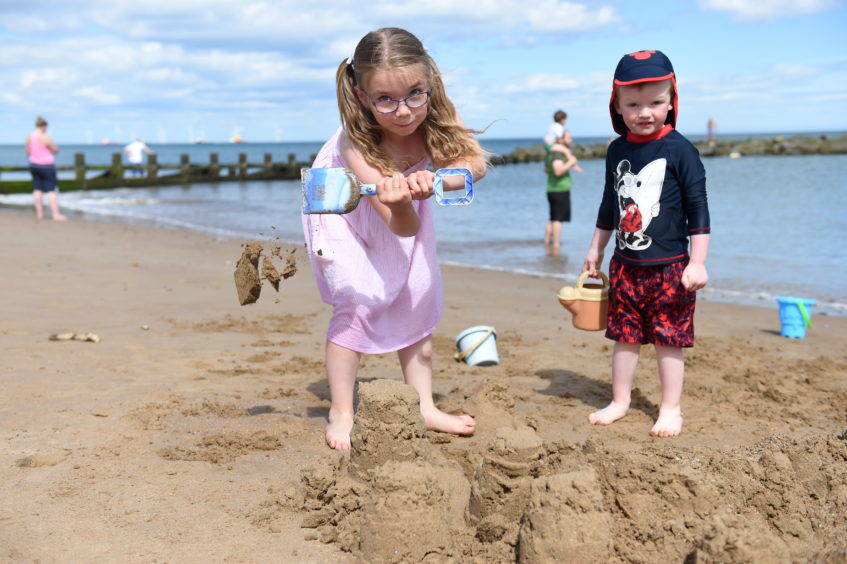Sophie building a sandcastle with the help of her brother