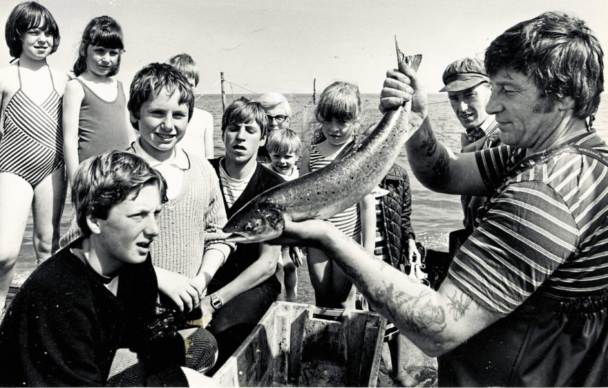 1984: A silver salmon from the nets at Aberdeen Beach holds the attention of youngsters and adults alike as fishermen Tommy Thomson and Bob Nicholson show the fish to the holiday makers