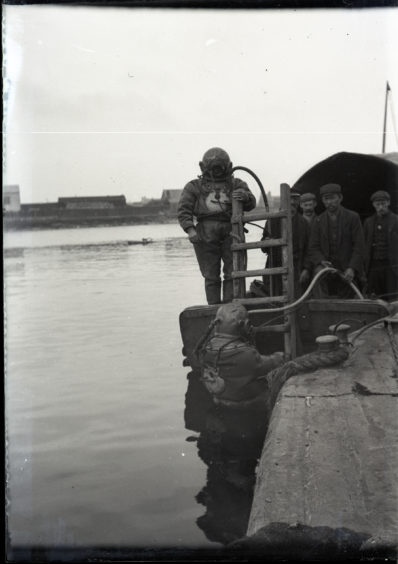 Diver and support boat at harbour