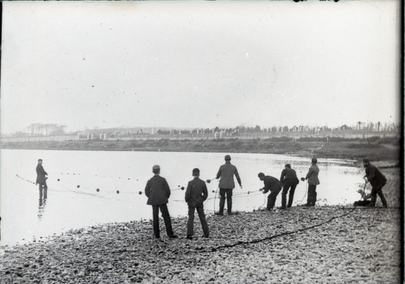 Group of men pulling fishing nets from river