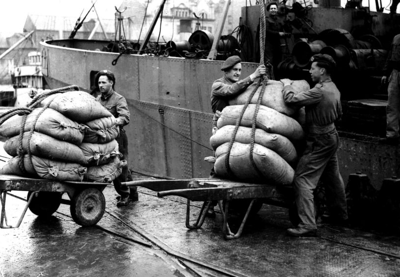 Military personnel working in the habour during a dock workers strike, 25th May 1945
