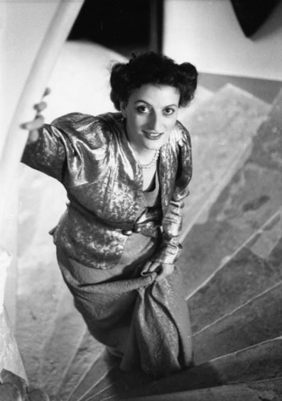 1987: Typical of the 1930s is an orange and lurex panelled evening dress with a silver lame figured lurex jacket. The dresses of this period were figure clinging and evening jackets usually had large collars.