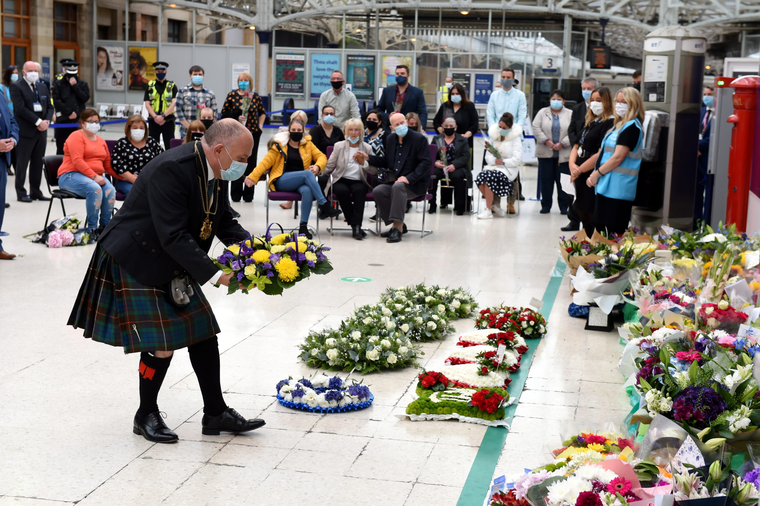 Aberdeen Lord Provost Barney Crockett lays a wreath under the station sign. Picture by Kenny Elrick