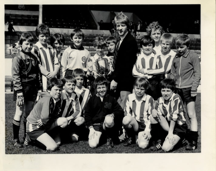 1982: Tillydrone Primary School football team captain Stanley McLean (centre) is presented with the Aberdeen Primary Schools FA's Willoughby Cup by Dons star Gordon Strachan.