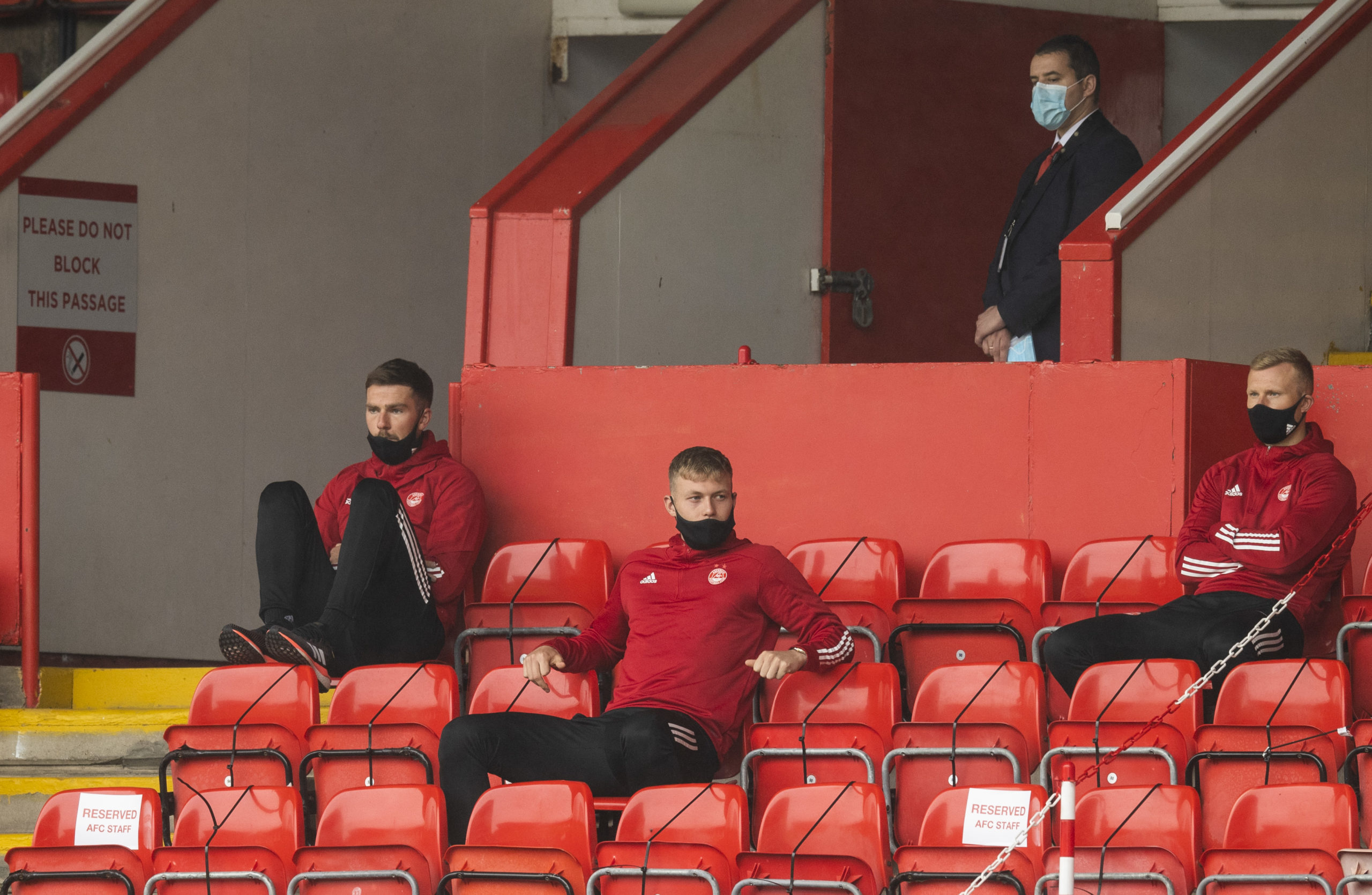 Aberdeen's Mikey Devlin, Sam Cosgrove and Curtis Main (L-R) watch on during the Scottish Premiership match between Aberdeen and Rangers.