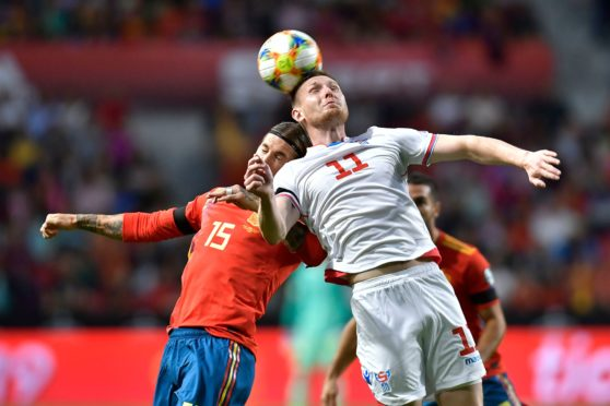Runavik's Olsen competes with Spain and Real Madrid's Sergio Ramos while on international duty with the Faroe Islands.
