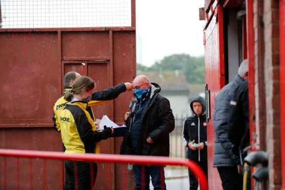 Willie Miller has his temperature checked ahead of the Ladbrokes Scottish Premiership match between Aberdeen and Rangers at Pittodrie Stadium.