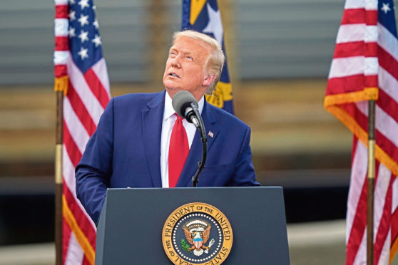 With the USS Battleship North Carolina in the background, President Donald Trump speaks on Wednesday, Sept. 2, 2020, in Wilmington, N.C. (AP Photo/Gerry Broome)
