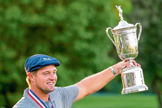 Bryson DeChambeau, of the United States, holds up the winner's trophy after winning US Open Golf Championship, Sunday, Sept. 20, 2020, in Mamaroneck, N.Y.