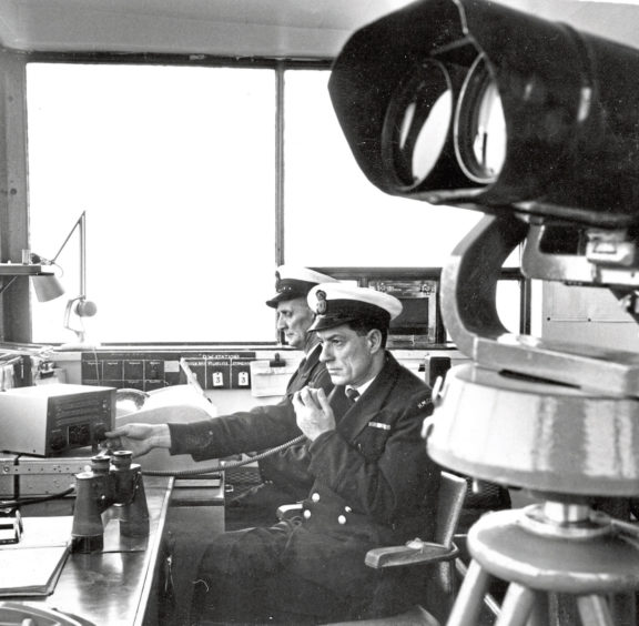 1970: Keeping the coast safe and manning the equipment at the Aberdeen Rescue headquarters at Gregness are Station Officer R Rainford, nearest the camera, and coastguard Charles Thompson. Their equipment included the huge German binoculars in the foreground, at one time the eyes of the officer on duty to keep a constant watch on the sea.