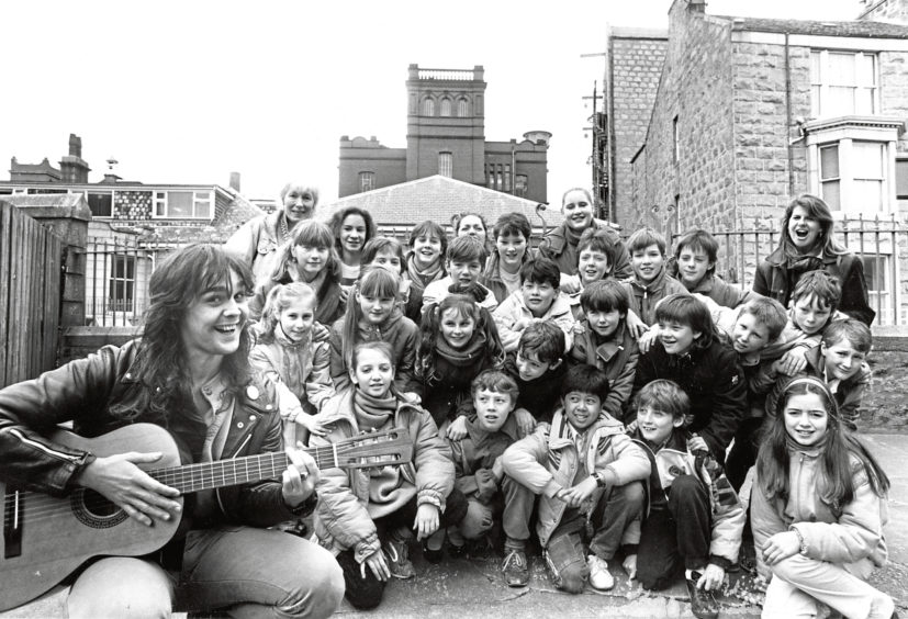 """1987: Musician Ally Craig with children from Room 25, Skene Square School, who will be performing in """"Fit A Turn-oot""""."""