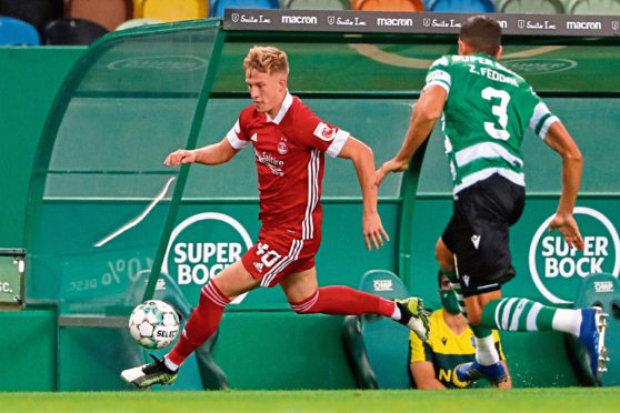 Aberdeen's Ross McCrorie runs with the ball past Sporting's Zouhair Feddal Agharbi.