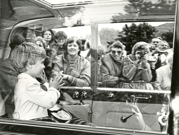 1987: Prince William waving at the crowds from the car, where he was sitting in between The Queen and the Duke of Edinburgh. The Royal family were going to Crathie Church.
