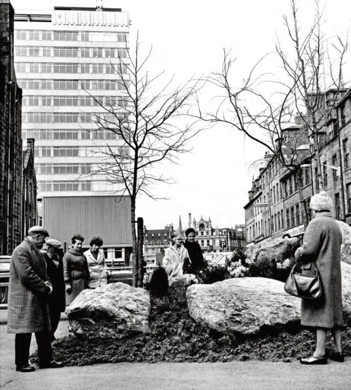 1970: Passers-by check out an 'instant garden' that council workers put up in one night on the former site of the city's tourist information bureau