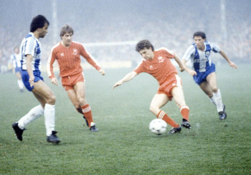 Mark McGhee looks on as teammate John Hewitt controls the ball.