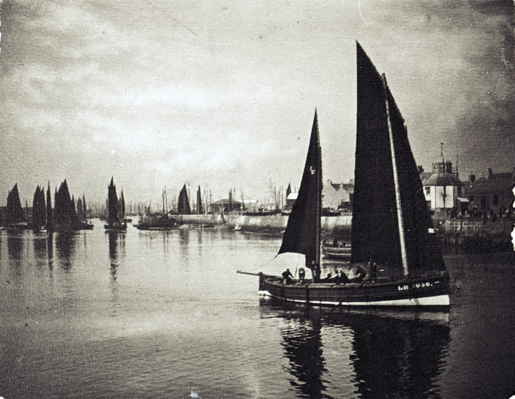 A Leith registered fifie leaving the harbour, passing Pocra Quay's Lower Basin and the Harbour Master's office on the New Quay. The fifie was a fast wind-powered sailing boat favoured for herring fishing on much of Scotland's east coast from the 1850s until well into the 20th century.