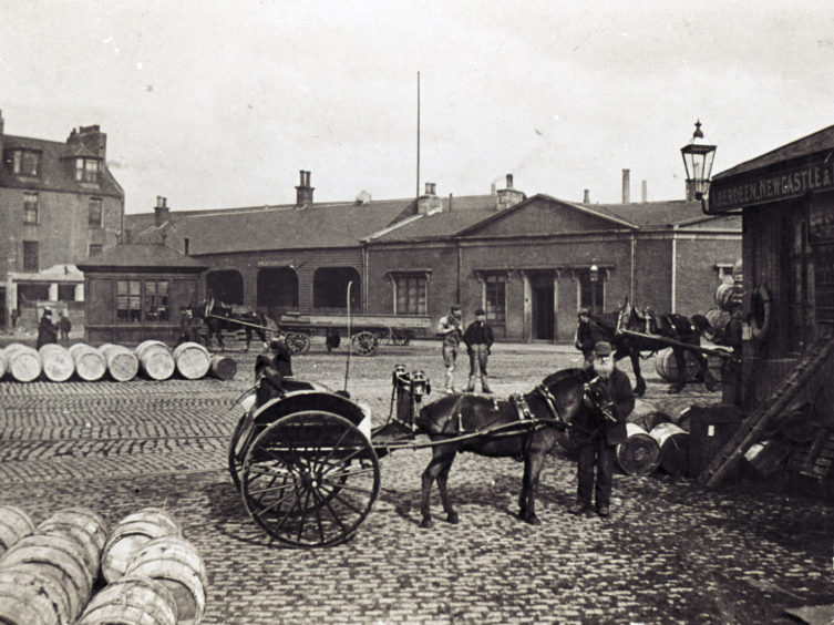 Late 19th century photograph showing junction of Regent Quay and Waterloo Quay. The building with the pediment is the offices of the Great North of Scotland Railway Company. To its left is the entrance to Waterloo Goods Station. Opened in 1856, the station was active into the mid-20th century.