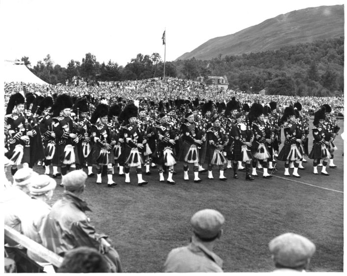 The massed pipe band march around the arena at the Braemar Highland Games.