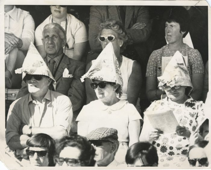 Spectators sought respite from the sun by putting their newspapers to good use.