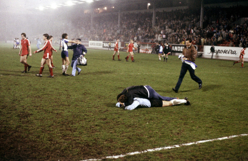 Porto players and supporters celebrate on the Pittodrie pitch at full-time.