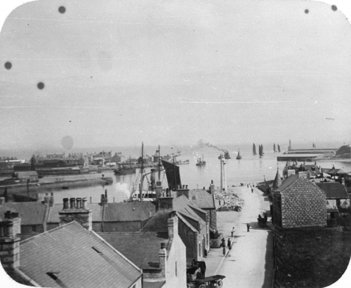 Across the harbour mouth, the village of Old Torry. This 19th century image looks east along Sinclair Road, towards its harbour, and out to sea. Old Torry developed in the early 19th century and was known for its architecture of narrow lanes and forestairs and the fishing way of life.