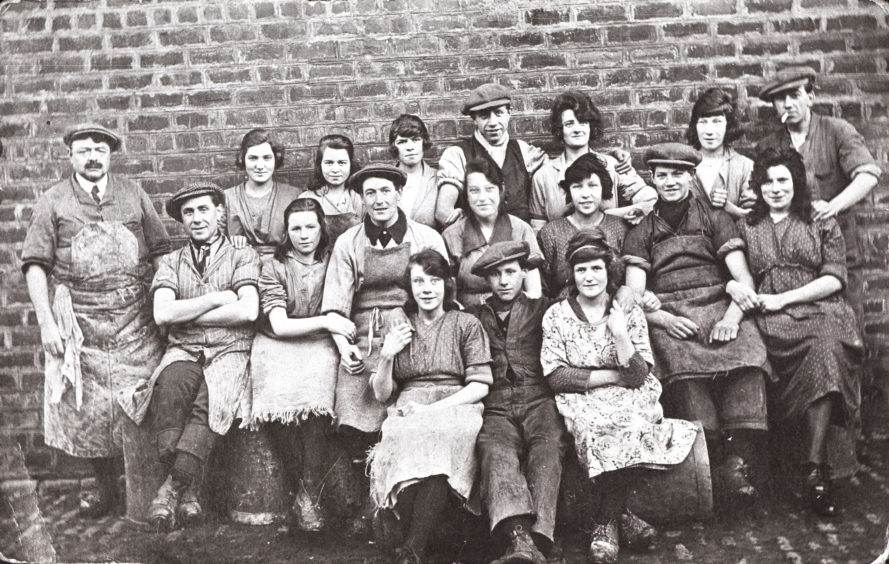 20th century portrait of workers from a fishcurers on Torry's Sinclair Road. The fishing industry created many jobs onshore especially following the boom of the 1880s. Fishcurers would gut and preserve fish for local and export markets. This could involve smoking, pickling, salting or air-drying fish.