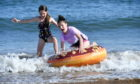 Sisters Niamh Kavanagh, 7,  left, and Lilly 11, making the most of the warm weather at the beach.
