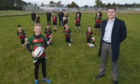 Aldi's area manager Neil Malcolm with top prize winners, Highland Rugby Football Club