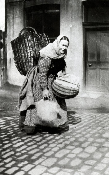 Torry fishwife with a creel on her back and a basket and shopping bag in her hands. Many fishwives walked miles into the centre of Aberdeen, and back, every day carrying heavy loads. Other time was spent mending nets, curing fish and on other domestic tasks.