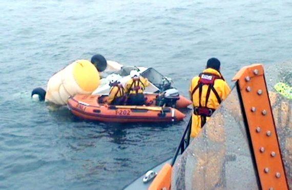 RNLI and coastguard volunteers inspecting the wreckage