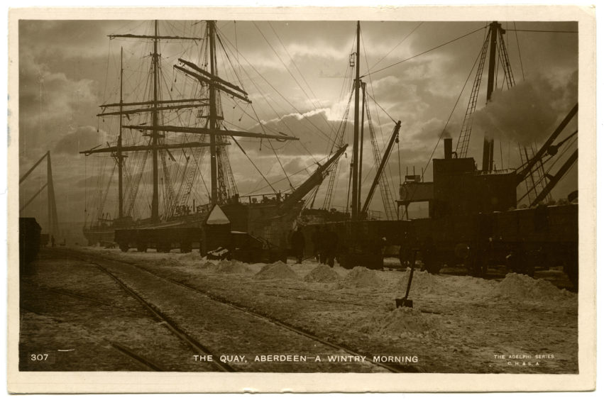 1910s postcard showing large sail ships moored in Victoria Dock at Waterloo Quay on a wintry morning. Great North of Scotland railway wagons are in the foreground and the 75- and 100-ton shear poles, a form of crane, can be seen at the North Lock in the background.