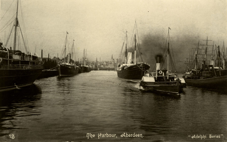 Early 20th century postcard looking north west along Victoria Dock in Aberdeen Harbour with the town centre in the background. The steam paddle tug John McConnachie is shown towing the Aberdeen Steam Navigation Company's passenger and cargo steamship the City of Aberdeen out to sea.