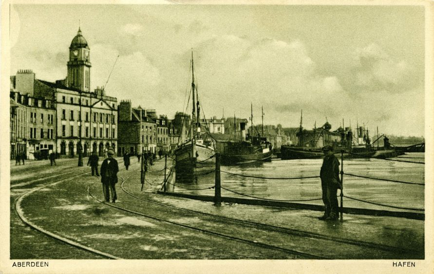 Postcard looking east from the junction of Market Street and Trinity Quay. Regent Quay, including the Harbour Board office, is on the left and, on the right, ships are moored in the Upper Dock. Wagon rails were used to transport goods around the harbour and to nearby good stations.