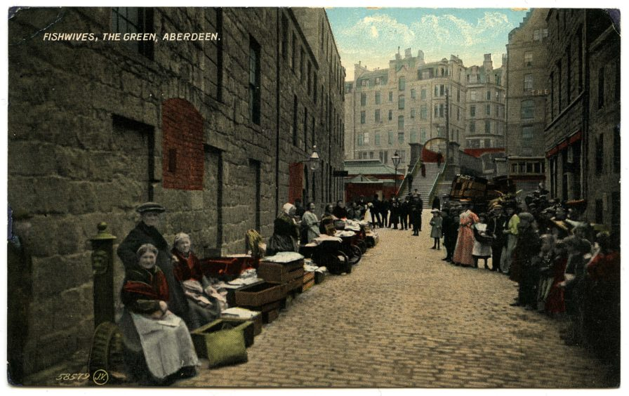 Postcard showing fishwives selling produce in Aberdeen's Green. Looking west, beyond the assembled crowds can be seen the Puffing Briggie that linked the Green and Windmill Brae across the train tracks.