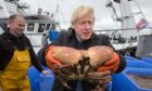 Prime Minister Boris Johnson holds crabs caught on the Carvela with Karl Adamson at Stromness Harbour during a visit on July 23 2020.