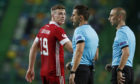 Aberdeen's Lewis Ferguson talks to referee Nikola Dabanovic, center, at the end of the Europa League third qualifying round soccer match between Sporting CP and Aberdeen.
