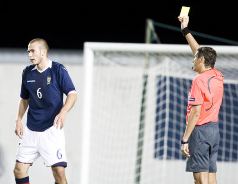 Andy Considine is booked for Scotland Under-21s against Slovenia in 2008.