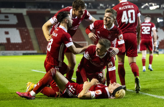 Lewis Ferguson is mobbed by his Dons team-mates.