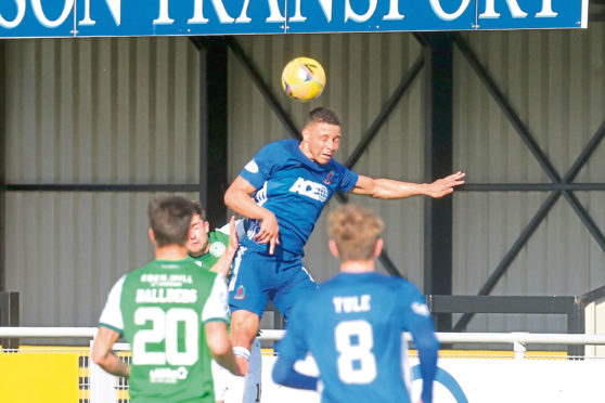 Leighton McIntosh goes up for a header against Hibs.