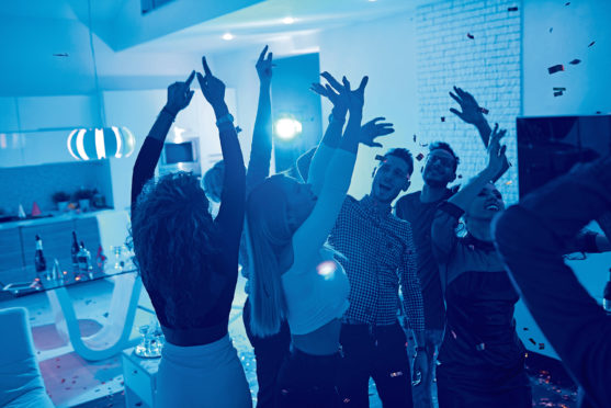 Group of modern young people dancing under confetti at private house party lit by blue light; Shutterstock ID 1050017789