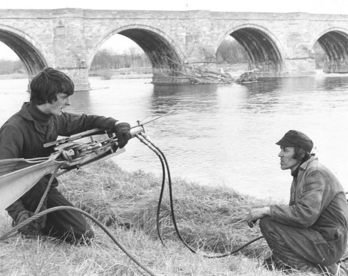 1979: Employees of Aberdeen firm Lifting Gear Hire Ltd., Riverside Drive, apprentice fitter Ian Nicol, and engineer Kenny Ross successfully winch a tree from the river at Bridge of Dee, Aberdeen, yesterday. The tree was washed downstream in the winter floods and had been lodged against the bridge for almost four months.