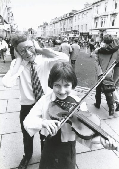 1989: Chin and bear it...Young violinist Anna Low, from Torphins, take a bow and tunes up to the mock consternation of Christopher Parker, Stonehaven, in Aberdeen's Union Street. Both are members of Aberdeen Music Centre preparatory string orchestra, who were playing in the city's Music Hall at the weekend to an audience of schoolmates, teachers and parents.