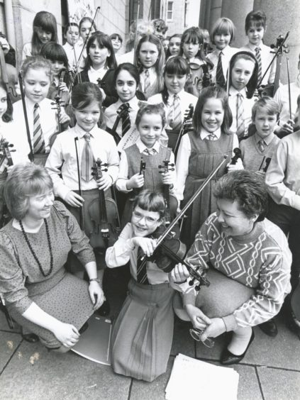 1989: Stringing along...Ten year old Rhona Donald (front centre), Westhill, with conductors Susan Simpson (left), Ellon, and Beverley Lithgow (right), Westhill, with other members of the Aberdeen Music Centre Beginners' String Orchestra who took part in a concert at Aberdeen Music Hall on Saturday.