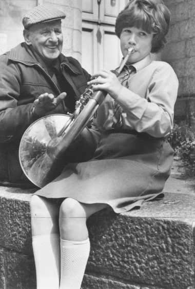 1984: Pensioner Alex England enjoys a tune from 10 year old Josephine Watson, of Gairn Terrace, Aberdeen, who won the French Horn 13 years and Under section.