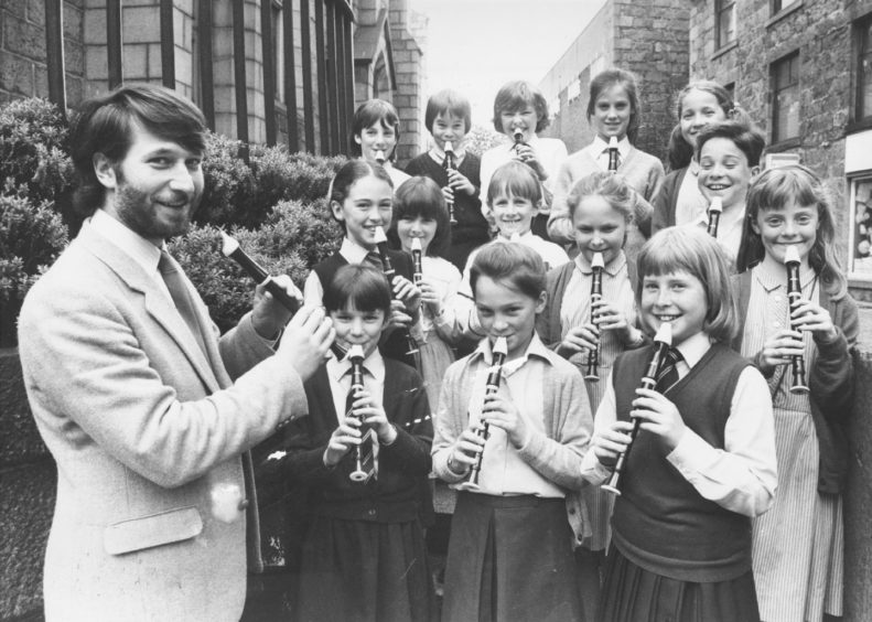 1986: Youngsters from Tarves, Udny Green and Aberdeen's St Margaret's School gather outside the Kirk House in Aberdeen during the music festival yesterday. Competitors in the descant solo contest for under nines, they were judged by Colin Touchin (extreme left).