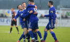 Daniel Higgins (centre) is congratulated by Cove players after his goal against Edinburgh City last season.