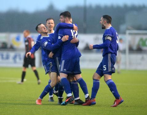Daniel Higgins (centre) is congratulated by Cove players after his goal against Edinburgh City last season.