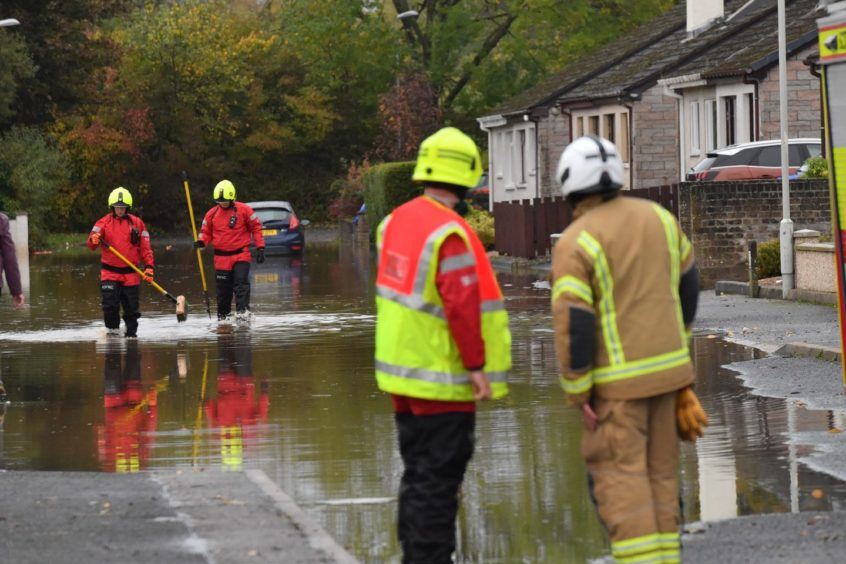 Firefighters survey the scene on Bruce Crescent in Ellon. Picture by Kami Thomson