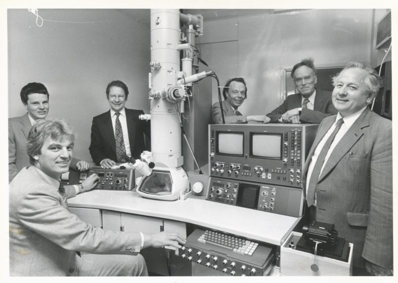 1984: At the controls of the Rowett's new microscope is makers representative Dr Tony Brown watched by (from left) Dr Tom King, Prof. Philip James, Prof. Frederick Walker, Dr Bernard Fell and also from the microscope company, Mr Houston Martin.